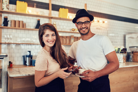 Young couple at cafe with a cup of coffee and digital tablet
