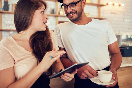 Young couple at cafe counter having discussion