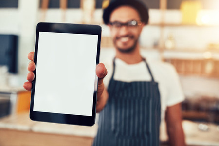Digital tablet in hand of cafe worker