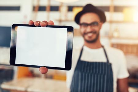 Digital tablet in hand of cafe owner