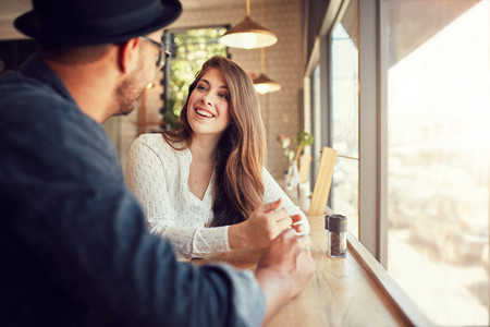 Smiling young woman at cafe with her boyfriend