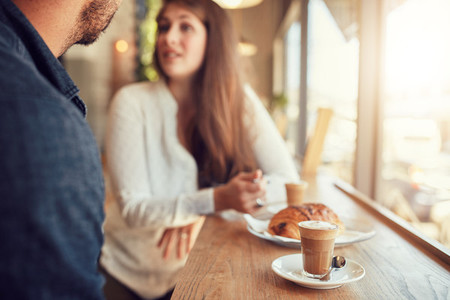 Cup of coffee and food on table with couple talking in cafe