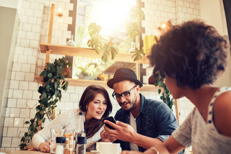 Young couple looking at smart phone while sitting in cafe