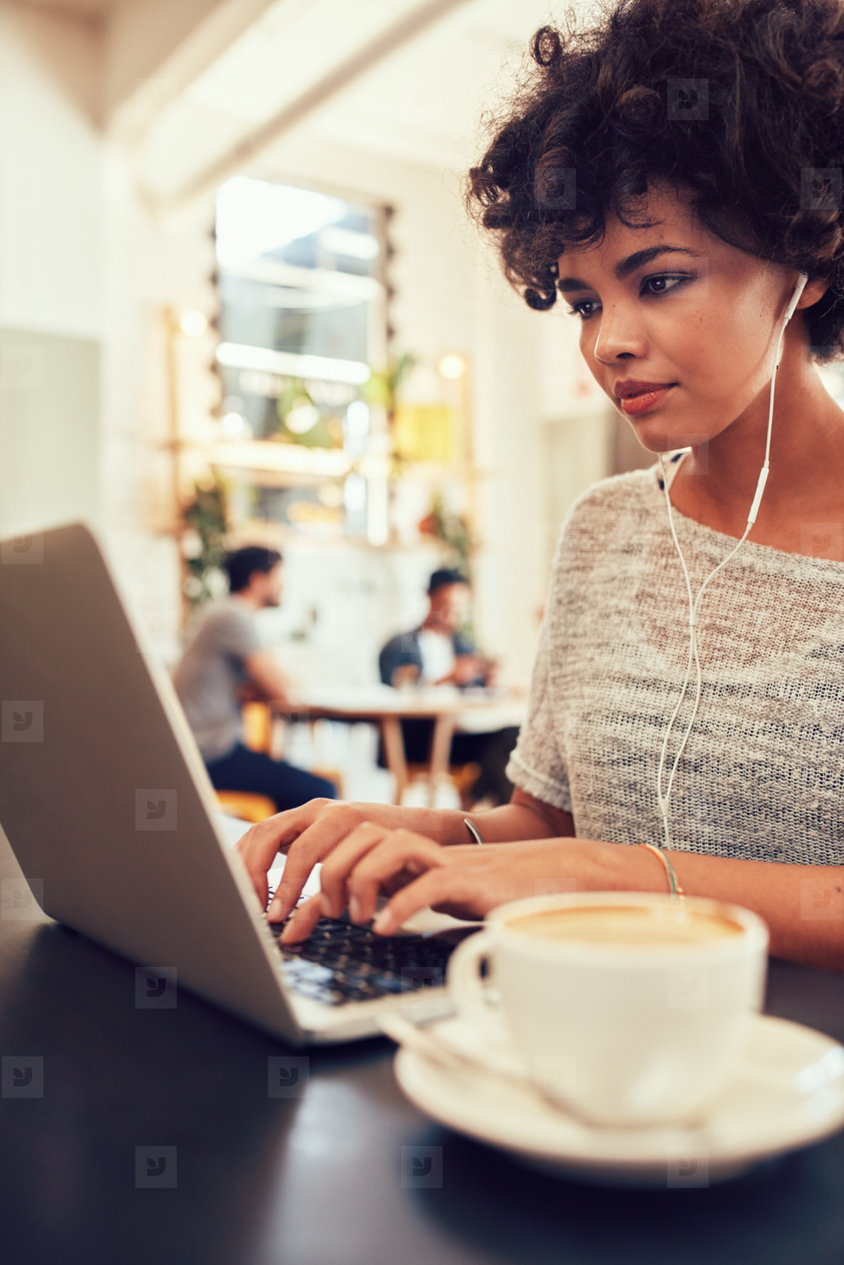 African woman at a coffee shop using laptop