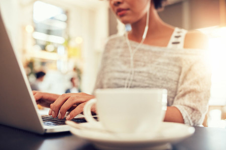 Woman sitting at a coffee shop working on laptop