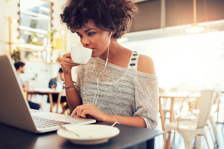 Young african woman drinking coffee and using laptop at a cafe