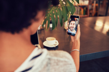 Woman having a videochat with friend on mobile phone