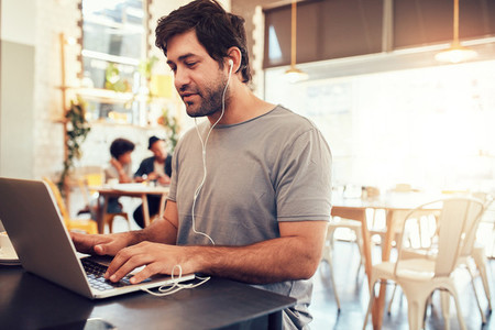 Young guy at a cafe surfing internet on laptop