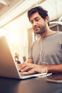 Caucasian man sitting in coffee shop using laptop