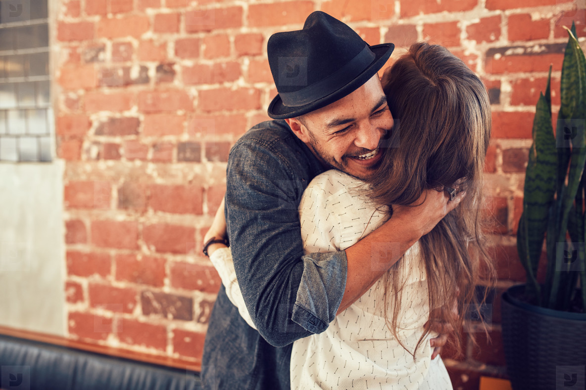 Young man hugging a woman in a coffee shop