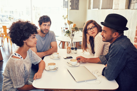 Young men and women sitting at a cafe