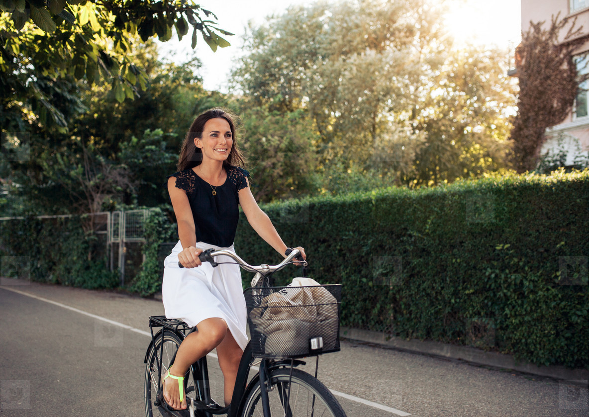 Beautiful young woman cycling along street
