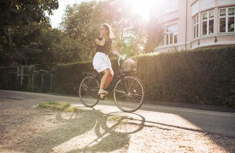 Woman enjoying bicycle ride through the street