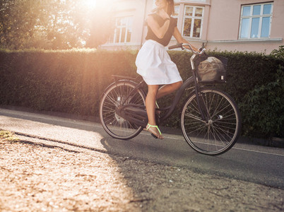 Woman riding bicycle along the street