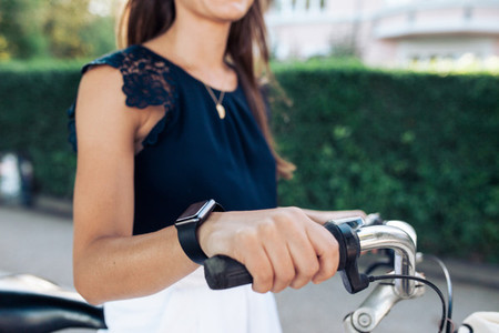 Woman on bicycle with a smartwatch