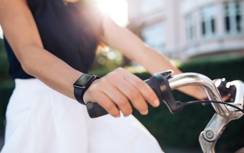 Woman riding bike with a smartwatch