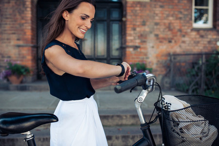 Woman with a bicycle looking at time on wristwatch