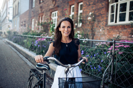 Beautiful woman with a cycle walking down the city road