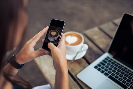 Woman photographing a coffee of cup with smart phone
