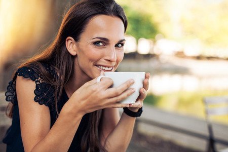 Cheerful woman enjoying a cup coffee