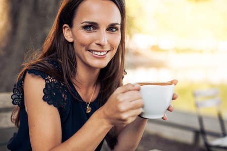 Smiling young woman with a cup of coffee