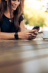 Woman using smart phone in a outdoor cafe
