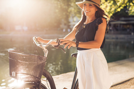 Pretty young woman with a bicycle in park