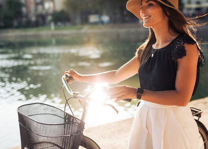 Cheerful young female at the park with her bicycle