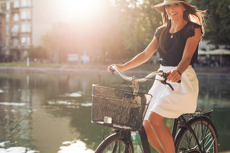 Attractive woman riding a bicycle by a pond