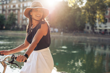 Happy young woman riding bicycle by a pond