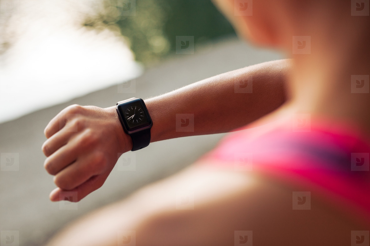 Sportswoman checking time on smartwatch