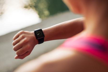 Sportswoman checking time on smartwatch