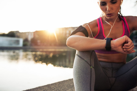 Runner checking her performance on fitness smart watch device