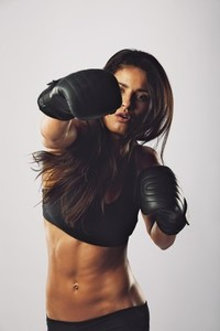 Hispanic female boxer practicing boxing