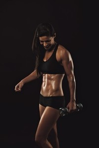 Happy young woman exercising with dumbbell