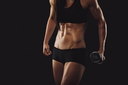 Strong and muscular build woman exercising with dumbbell