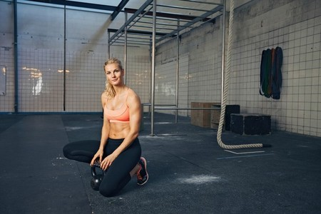 Sports woman at crossfit gym with kettlebell