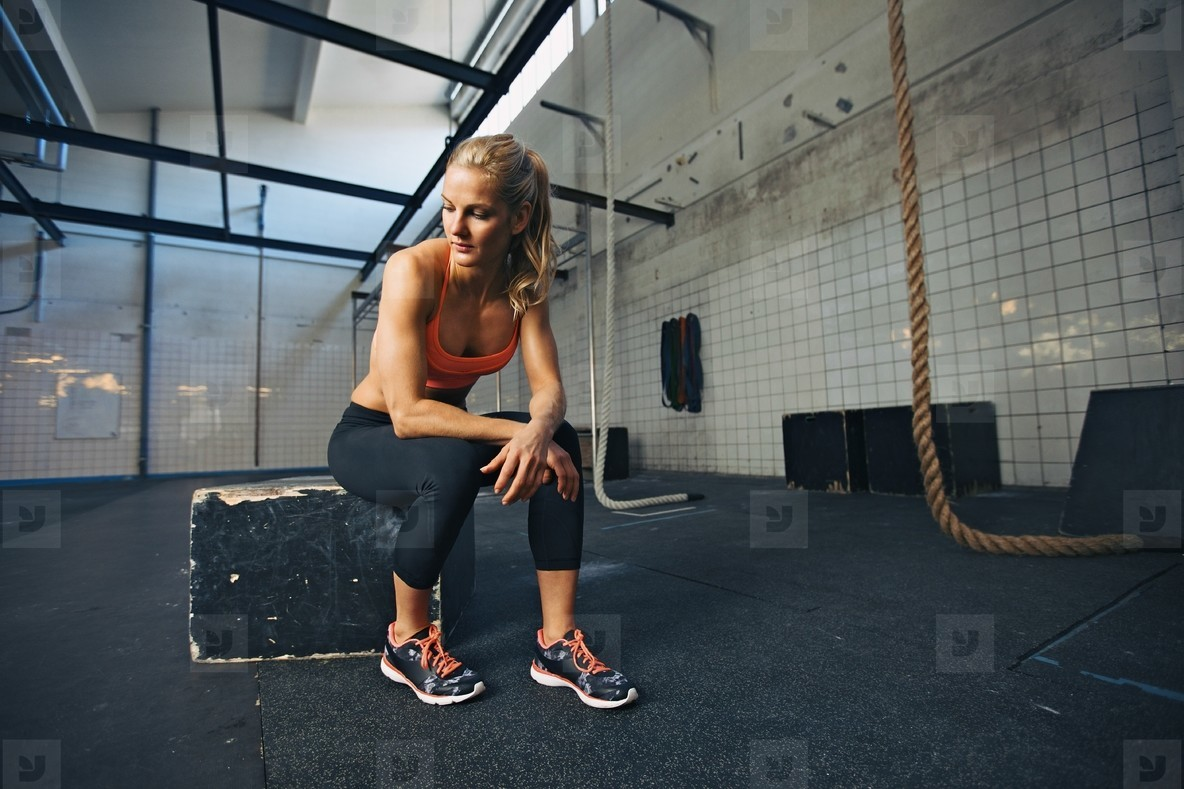 Fit young woman taking break after workout at gym