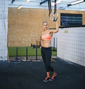 Fit young woman at gym with gymnast rings