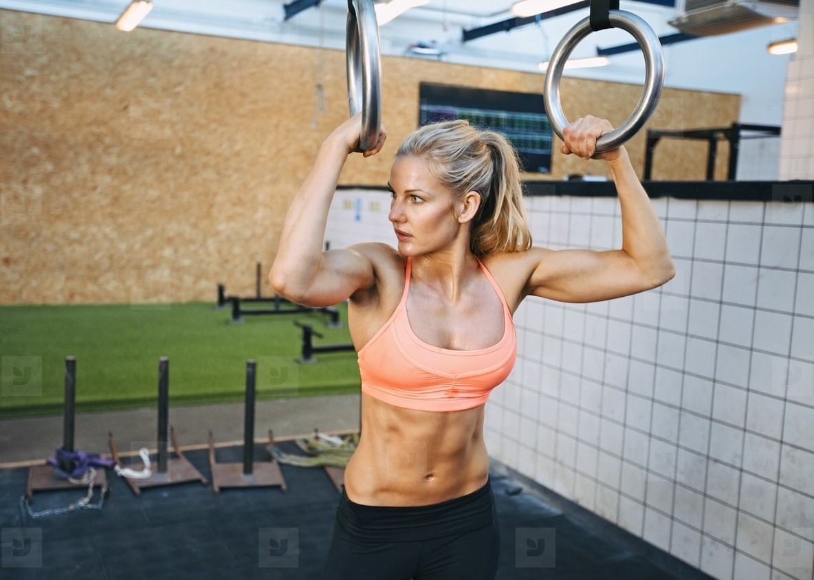 Fit young woman exercises with gymnast rings