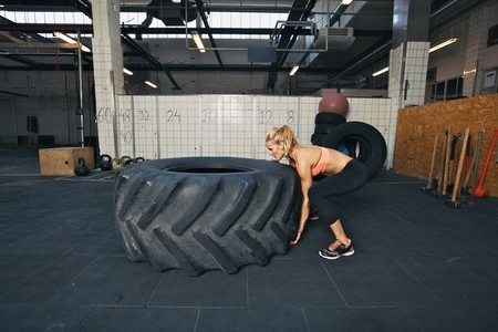 Female athlete flipping a tire while working out