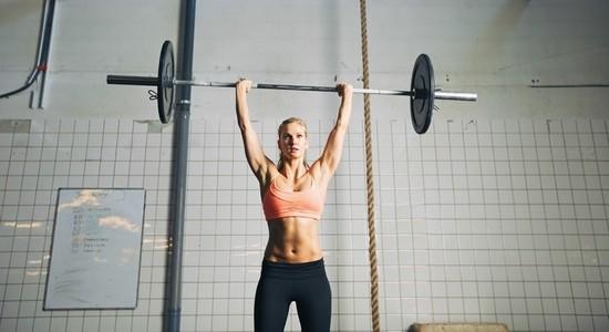 Fitness woman lifting barbells