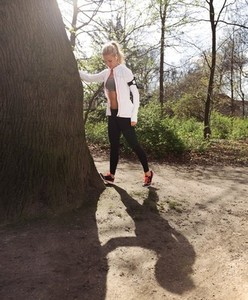 Young woman stretching before a jog in forest