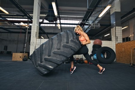 Crossfit woman flipping a huge tire at gym