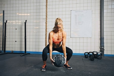 Woman doing crossfit workout with medicine ball  at gym