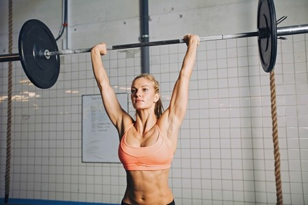 Fit young female athlete lifting heavy weights
