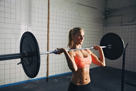 Strong woman lifting weights in crossfit gym