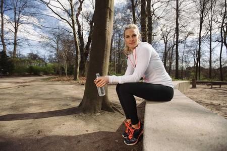 Female runner taking a break from running in forest