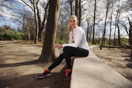 Female runner taking a rest from training in nature