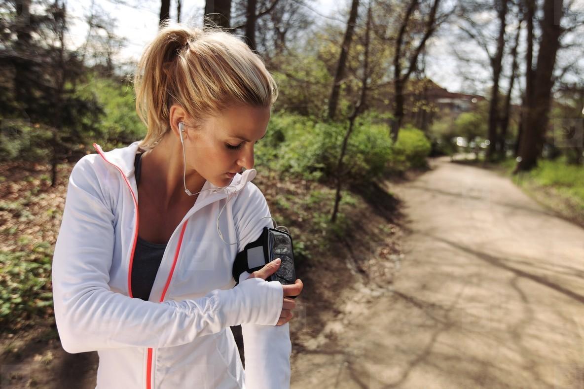 Female runner monitor her progress on smartphone